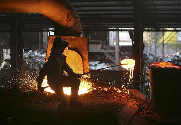 A labourer works inside a steel factory on the outskirts of Jammu January 2, 2014. REUTERS/Mukesh Gupta