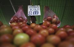 Vendedos ergue sacolas de tomates em feira livre no bairro da Mooca, em São Paulo. Pressionado por preços de alimentos, o Índice Nacional de Preços ao Consumidor Amplo (IPCA) encerrou 2013 com alta de 5,91 por cento, dentro da meta oficial mas acima do resultado do ano anterior, frustrando o objetivo final do governo. 4/05/2013. REUTERS/Nacho Doce