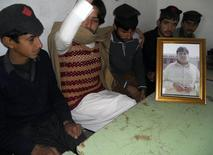 Mujtaba Hussan (2nd L), brother of Aitezaz Hassan who was killed in a suicide bomb attack, sits with students of the high school next to a framed portrait of Hassan in a classroom at the Government High School Ibrahim Zai in Hangu district, bordering North Waziristan January 10, 2014. REUTERS/Syed Nadeem