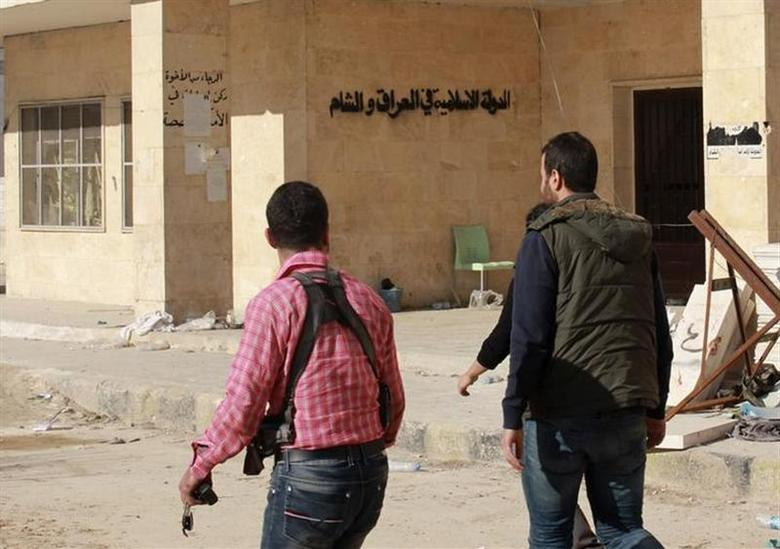 Rebel fighters walk at the former stronghold of fighters from the Islamic State in Iraq and the Levant (ISIL), after it was captured by them in Aleppo January 8, 2014. REUTERS/Abdalrhman Ismail