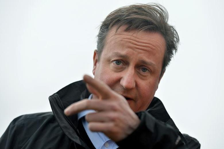 Britain's Prime Minister David Cameron speaks to local firefighters, during a visit following the recent storms and flooding, in Yalding, southern England December 27, 2013. REUTERS/Ben Stansall/Pool