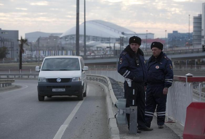 Russian traffic police officers stand guard during patrol on a road near venues at the Olympic Park near Sochi January 7, 2014. REUTERS/Kazbek Basayev