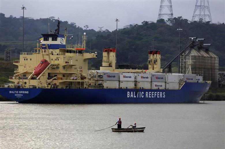 Panama workers are seen in a boat next to a cargo ship in the pacific side of the Panama Canal in Panama City January 8, 2014. REUTERS/ Carlos Jasso