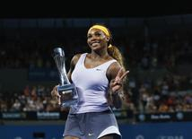 Serena Williams of the U.S. holds up the Brisbane International trophy after defeating Victoria Azarenka of Belarus in the women's singles final in Brisbane, January 4, 2014. REUTERS/Jason Reed