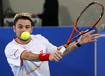 Stanislas Wawrinka of Switzerland hits a return to David Ferrer of Spain during Mubadala World Tennis Championship in Abu Dhabi December 26, 2013. REUTERS/Ahmed Jadallah