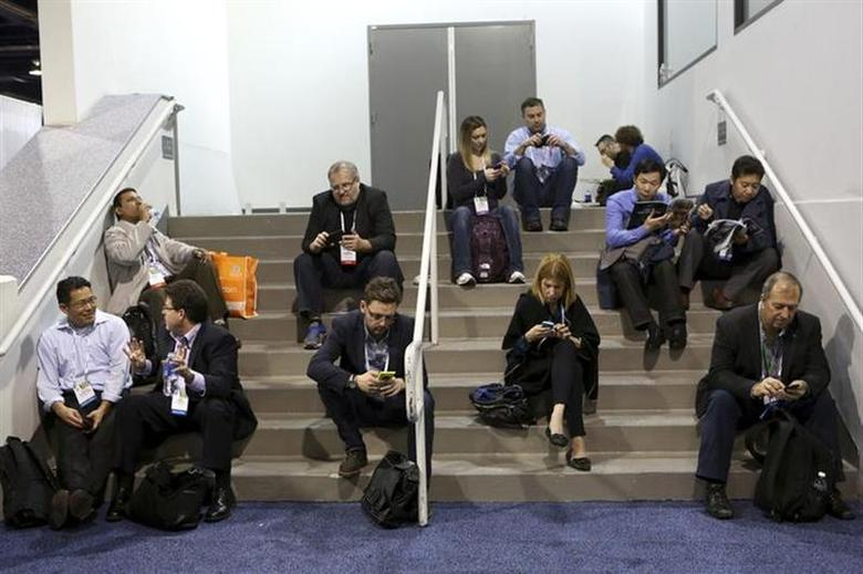 People work on their mobile devices at the annual Consumer Electronics Show (CES) in Las Vegas, Nevada January 8, 2014. REUTERS/Robert Galbraith