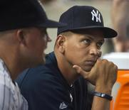 New York Yankees third baseman Alex Rodriguez sits in the dugout with teammate first baseman Casey McGehee (L) and watches his team play the Seattle Mariners in their MLB American League game at Yankee Stadium in New York, August 3, 2012 file photo. REUTERS/Ray Stubblebine