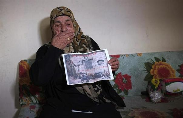 Milany Boutros Alha Bourje holds a picture of herself, standing over her dead family after the Sabra and Shatila massacre, in her home at the Shatila Palestinian refugee camp on the outskirts of Beirut January 11, 2014. REUTERS-Caren Firouz