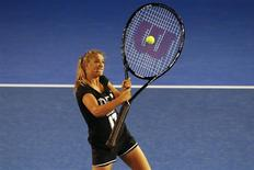 Victoria Azarenka of Belarus hits a ball with an oversized tennis racquet during the Kids Tennis Day before the Australian Open 2014 tennis tournament in Melbourne, January 11, 2014. REUTERS/David Gray
