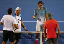 Roger Federer of Switzerland (2nd R) smiles as he goes to shake hands with Rafael Nadal of Spain (R) as Lleyton Hewitt of Australia (2nd L) and compatriot Patrick Rafter shake hands during the Kids Tennis Day before the Australian Open 2014 tennis tournament in Melbourne, January 11, 2014. REUTERS/David Gray