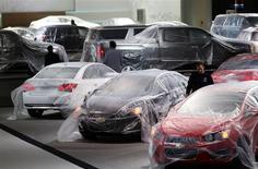 """Préparatifs sur le stand de General Motors à Detroit. Le salon automobile de Detroit confirmera la semaine prochaine la normalisation du marché américain face à une Europe au mieux convalescente, et donnera la vedette aux imposants 4X4 et aux """"muscle cars"""", toujours incontournables aux Etats-Unis. /Photo prise le 11 janvier 2014/REUTERS/Rebecca Cook"""