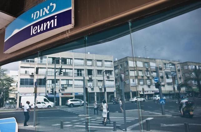 Pedestrians are reflected in the windows of a Bank Leumi branch in Tel Aviv May 30, 2013. REUTERS/Nir Elias