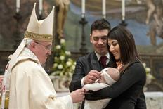 Pope Francis baptises one of 32 babies during a mass in the Sistine Chapel at the Vatican January 12, 2014, in this handout courtesy of Osservatore Romano. REUTERS/Osservatore Romano/Handout via Reuters