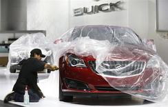 Auto show worker Jorge Martinez details a General Motors 2014 Buick Regal vehicle under wraps, as they prepare the displays for the media preview of the North American International Auto Show at Cobo Center in Detroit, Michigan January 11, 2014. REUTERS/Rebecca Cook