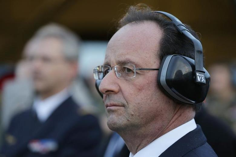 French President Francois Hollande wears protection for his ears as he watches a Mirage 2000-5 which taxis out of its hangar during a visit to the Creil military airbase as he presents New Year wishes to the French Army in Creil, near Paris, January 8, 2014. REUTERS/Philippe Wojazer