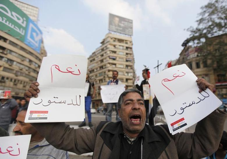 A supporter of Egypt's army chief and defense minister General Abdel Fattah al-Sisi holds signs during a protest in support of the new constitution at Tahrir Square in Cairo December 20, 2013. REUTERS/Mohamed Abd El Ghany