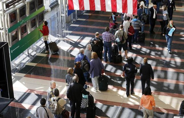 A line of passengers wait to enter the security checkpoint before boarding their aircraft at Reagan National Airport in Washington, April 25, 2013. REUTERS/Larry Downing