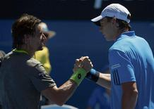 David Ferrer of Spain clasps hands with Alejandro Gonzalez of Colombia after winning their men's singles match at the Australian Open 2014 tennis tournament in Melbourne January 13, 2014. REUTERS/David Gray