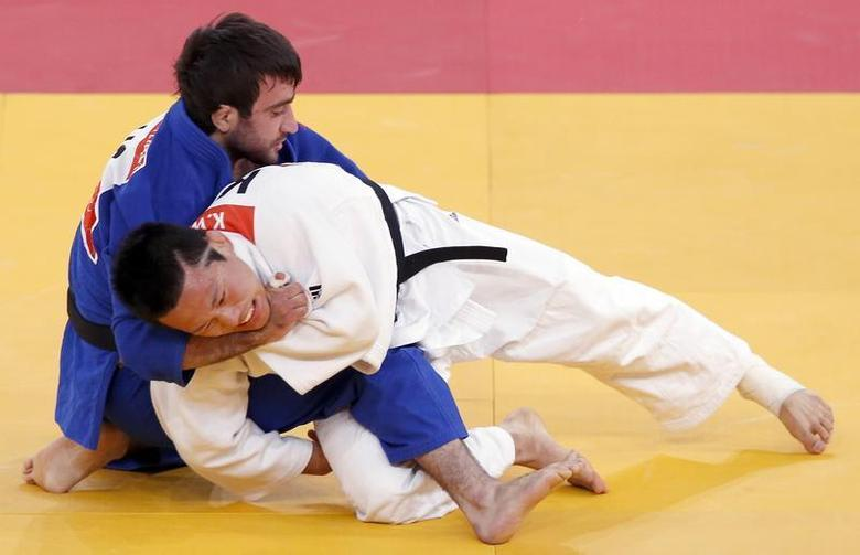 South Korea's Wang Ki-Chun fights with Russia's Mansur Isaev (blue) during their men's -73kg semi-final A judo match at the London 2012 Olympic Games July 30, 2012. REUTERS/Kim Kyung-Hoon