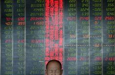 """Инвестор сидит у экрана с рыночными котировками в брокерской конторе в городе Тайюань в провинции Шаньси 9 мая 2013 года. Пять китайских компаний сообщили в понедельник, что откладывают первоначальное публичное размещение акций (IPO), что стало неприятностью для Пекина, который стремится передать рыночным силам """"решающую"""" роль на фондовых биржах страны. REUTERS/Jon Woo"""