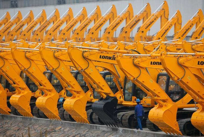 A worker walks past new excavators at a Lonking factory in Shanghai March 1, 2011. REUTERS/Aly Song