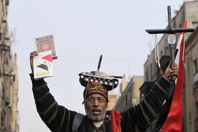 A supporter of Egypt's army chief and defense minister General Abdel Fattah al-Sisi holds a Koran (L) and a cross during a protest in support of the new constitution at Tahrir Square in Cairo December 20, 2013. REUTERS/Mohamed Abd El Ghany
