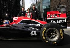 CNBC presenter Ross Westgate (L), Marussia Virgin Formula One driver Timo Glock (C), and the team's Chief Executive Officer, Graeme Lowdon, pose with an MVR-02 for a photograph in London March 14, 2011. REUTERS/Stefan Wermuth