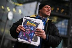 Unemployed street newspaper vendor Karsten offers the Strassenfeger (Street Sweeper) street newspaper and its Superhobo comic supplement in front of the main train station in Berlin January 13, 2014. REUTERS/Thomas Peter