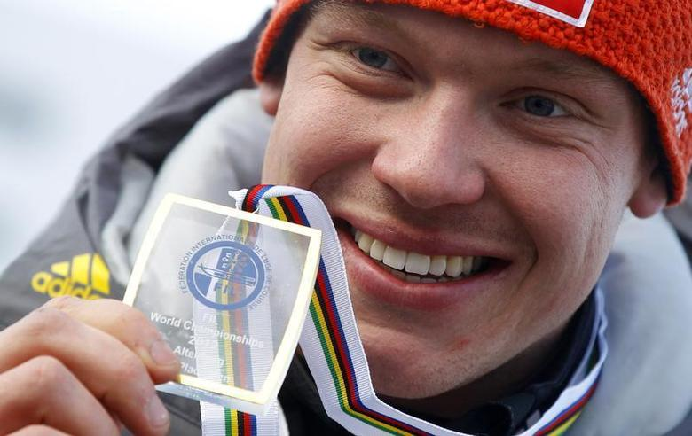 Germany's Felix Loch presents his gold medal after winning the FIL Luge World Championships in Altenberg February 11, 2012. REUTERS/Dominic Ebenbichler