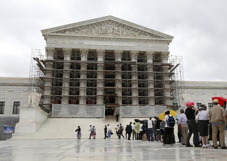 Visitors to the Supreme Court are pictured in the rain in Washington, October 7, 2013. REUTERS/Jason Reed