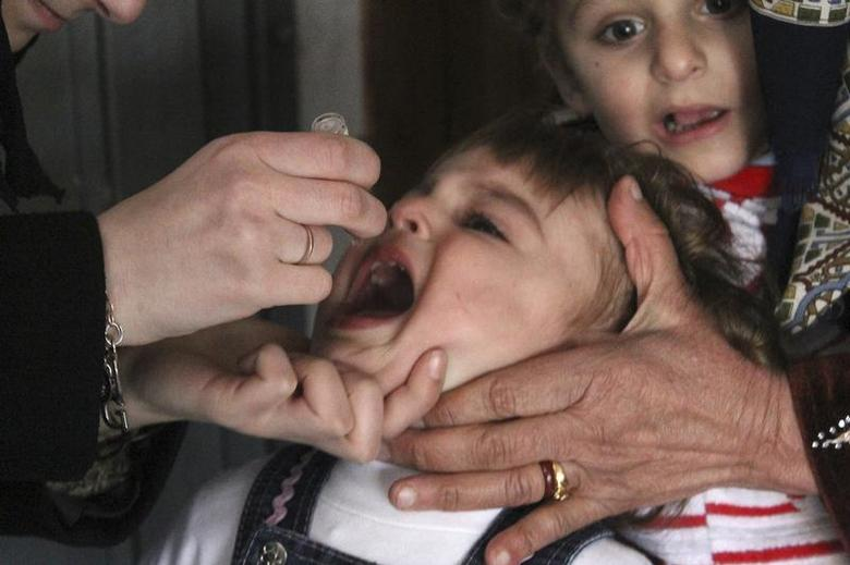 An activist health worker administers a polio vaccination to a child in Aleppo January 5, 2014. REUTERS/Hosam Katan