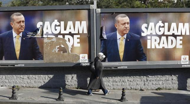 A woman walks past by billboards with pictures of Turkish Prime Minister Tayyip Erdogan, in Istanbul January 13, 2014. REUTERS/Murad Sezer
