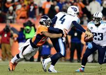 Dec 8, 2013; Denver, CO, USA; Denver Broncos cornerback Chris Harris (25) tackles Tennessee Titans quarterback Ryan Fitzpatrick (4) in the fourth quarter at Sports Authority Field at Mile High. The Broncos defeated the Titans 51-28. Mandatory Credit: Ron Chenoy-USA TODAY Sports - RTX16AEF