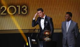 Portugal's Cristiano Ronaldo (L) gestures beside Pele after being awarded the FIFA Ballon d'Or 2013 in Zurich January 13, 2014. Portugal and Real Madrid forward Cristiano Ronaldo was named the world's best footballer for the second time on Monday, preventing his great rival Lionel Messi from winning the award for a fifth year in a row. REUTERS/Ruben Sprich