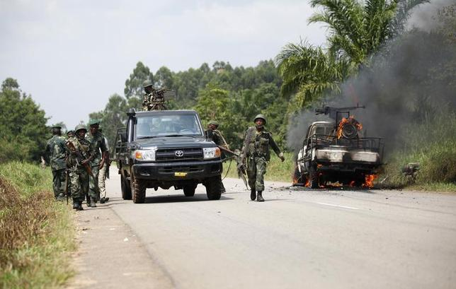 Congolese soldiers from the Armed Forces of the Democratic Republic of Congo (FARDC) stand next to their burning vehicle after an ambush near the village of Mavivi in North Kivu province January 2, 2014. REUTERS/Kenny Katombe