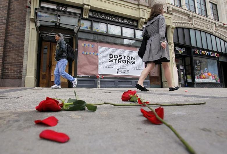 Flowers lie on the sidewalk at the site of the first explosion as people walk along Boylston Street after the street reopened to the public for the first time since the Boston Marathon bombings in Boston, Massachusetts April 24, 2013. REUTERS/Jessica Rinaldi