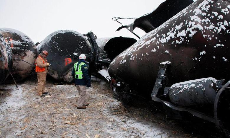 National Transporation and Safety Board (NTSB) member Robert Sumwalt (R) views damaged rail cars at the scene of the BNSF train accident in Casselton, North Dakota January 1, 2014 in this handout provided by NTSB. REUTERS/NTSB/Handout via Reuters