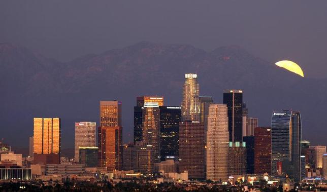 The Los Angeles downtown skyline is pictured from the Baldwin Hills State Park as a full moon rises from the San Gabriel mountains in Culver City, California October 12, 2011. REUTERS/Mario Anzuoni