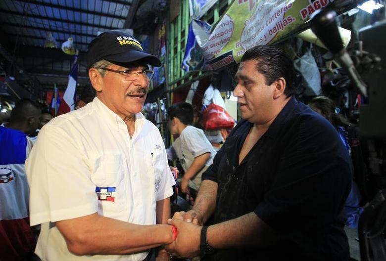 Norman Quijano (L), presidential candidate from the conservative Nationalist Republican Alliance party (ARENA), shakes hands with a man at a local market in La Libertad January 8, 2014. REUTERS/Ulises Rodriguez