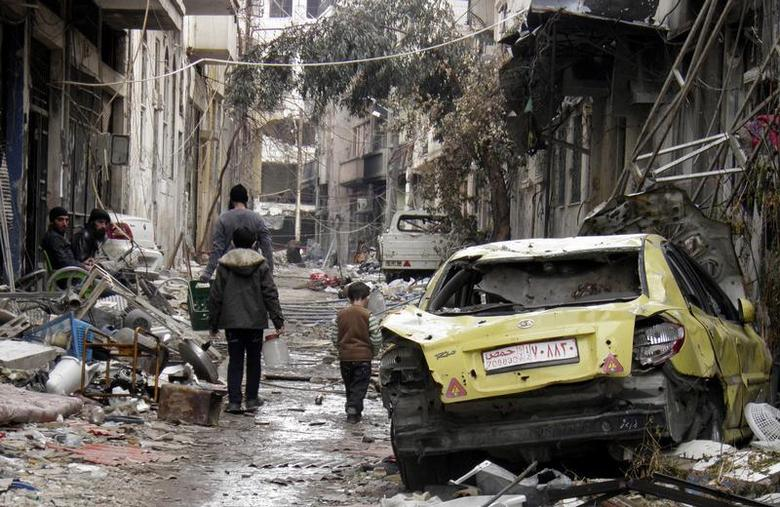 People walk past a damaged car along a damaged street in the besieged area of Homs January 13, 2014. REUTERS/Thaer Al Khalidiya