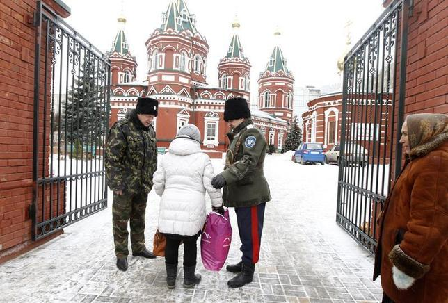Russian Cossacks, who started regular patrols within the city in the wake of recent suicide attacks, check a woman's belongings in front of the Kazan Orthodox Cathedral in the southern Russian city of Volgograd, January 4, 2014. REUTERS/Vasily Fedosenko