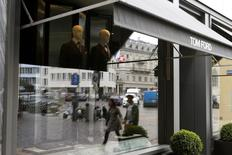 People are reflected in a window as they walk past a store of U.S. fashion designer Tom Ford, operated in Switzerland by luxury goods chain Trois Pommes, in Zurich August 9, 2013. REUTERS/Arnd Wiegmann