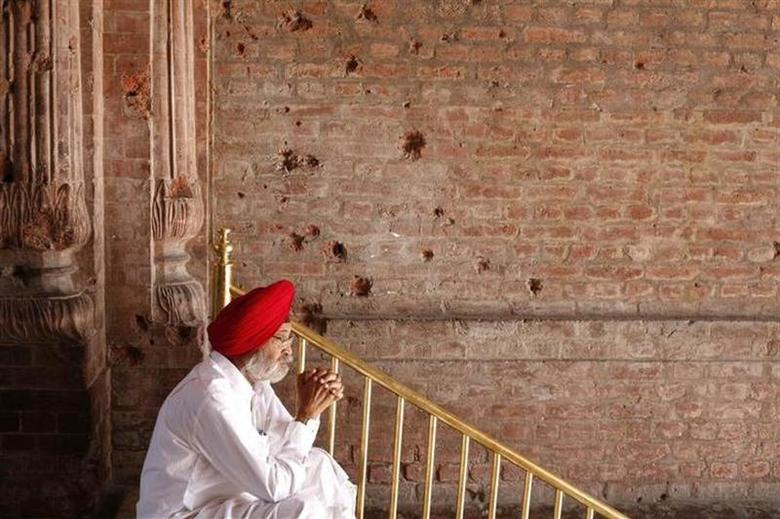 A Sikh man sits beside the wall of one of the complex of Golden Temple hit by the bullet shots during the operation Blue Star in Amritsar June 6, 2010. REUTERS/Yasir Iqbal/Files