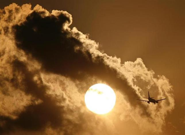 A passenger aircraft is silhouetted against the setting sun as it prepares to land at the airport in New Delhi September 5, 2009. REUTERS/B Mathur/Files