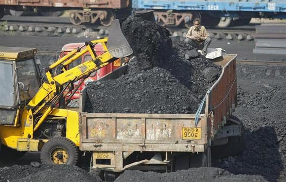 A worker sits on a truck being loaded with coal at a railway coal yard on the outskirts of Ahmedabad November 25, 2013. REUTERS/Amit Dave/Files