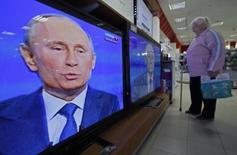 Женщина смотрит телепередачу с президентом России Владимиром Путиным в магазине электроники в Сочи 25 апреля 2013 года. Россия на пять лет запретила въезд журналисту из США, который критиковал Путина, что может ещё ухудшить отношения с Вашингтоном и напомнило о временах холодной войны. REUTERS/Alexander Demianchuk