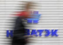Человек проходит мимо логотипа Новатэка в Москве 16 сентября 2012 года. Крупнейший российский частный производитель газа Новатэк закрыл сделку по продаже китайской CNPC 20 процентов в своем проекте производства сжиженного природного газа (СПГ) на Ямале. REUTERS/Maxim Shemetov