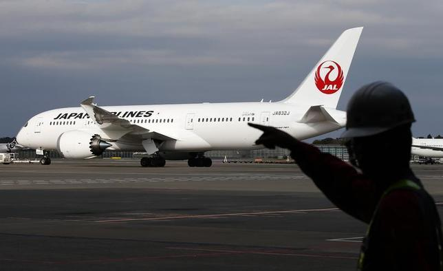 A staff of Japan Airlines' (JAL) walks past one of the company's Boeing Co's 787 Dreamliner plane at Narita international airport in Narita, east of Tokyo, November 11, 2013. REUTERS/Toru Hanai