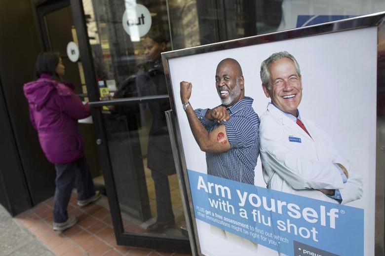 People enter a pharmacy next to a sign promoting flu shots in New York January 10, 2013. REUTERS/Andrew Kelly