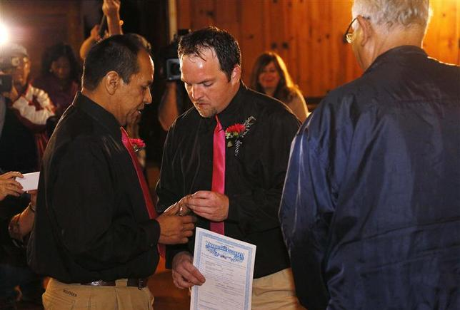 Darren Black Bear (L) and Jason Pickel exchange rings as they are married by Darren's father Rev. Floyd Black Bear (R) under a Cheyenne Arapahoe tribal licence in El Reno, Oklahoma in an October 31, 2013 file photo. REUTERS/Rick Wilking/Files